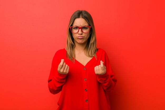 Joven auténtica mujer carismática de gente real contra una pared mostrando que no tiene dinero.