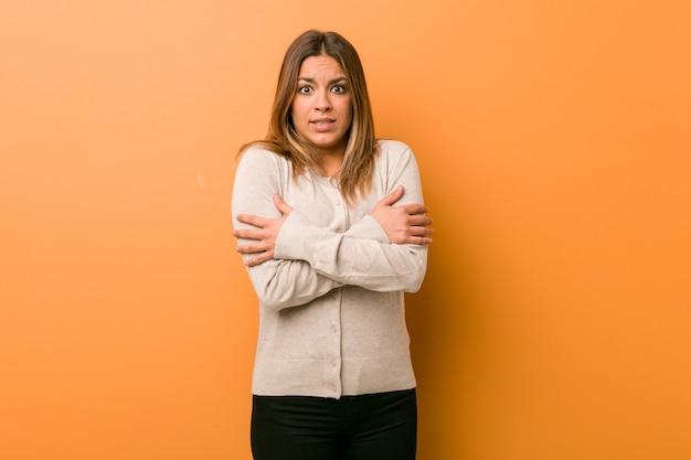 Joven auténtica mujer carismática de personas reales contra una pared que se enfría debido a la baja temperatura o una enfermedad.