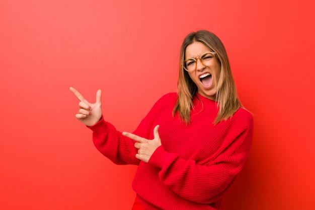 Joven auténtica mujer carismática de personas reales contra una pared que señala con el dedo índice a un espacio de copia, expresando emoción y deseo.
