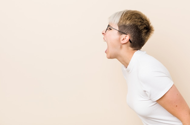 Joven auténtica mujer natural con una camisa blanca gritando hacia un