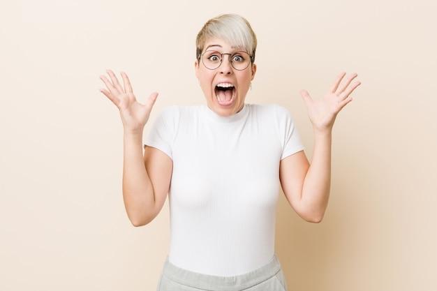 Joven auténtica mujer natural con una camisa blanca que celebra una victoria o éxito, está sorprendido y conmocionado.
