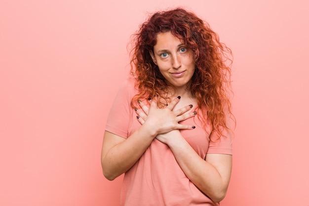La joven y auténtica mujer pelirroja tiene una expresión amigable, presionando la palma contra el pecho