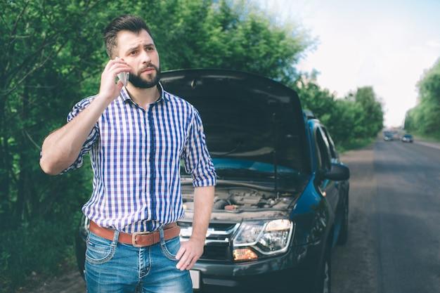 Un joven con un automóvil negro que se descompuso en la carretera y está llamando al técnico para que llegue.