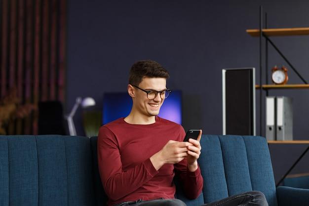 Joven autónomo con smartphone y sonriendo. hombre feliz usando aplicaciones de teléfono móvil, enviando mensajes de texto, navegando por internet, mirando el teléfono inteligente, sentado en casa. jóvenes que trabajan con dispositivos móviles.