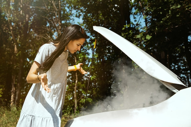 La joven averió el coche mientras viajaba camino de descansar. ella está tratando de arreglar el daño por su cuenta o debería hacer autostop. poniéndose nervioso