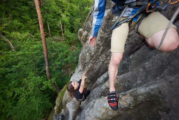 Joven ayudando a la niña a subir la cima de la montaña rocosa.