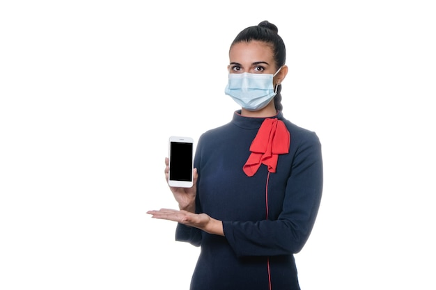 Joven azafata de aire en uniforme con mascarilla para prevenir la pandemia de coronavirus
