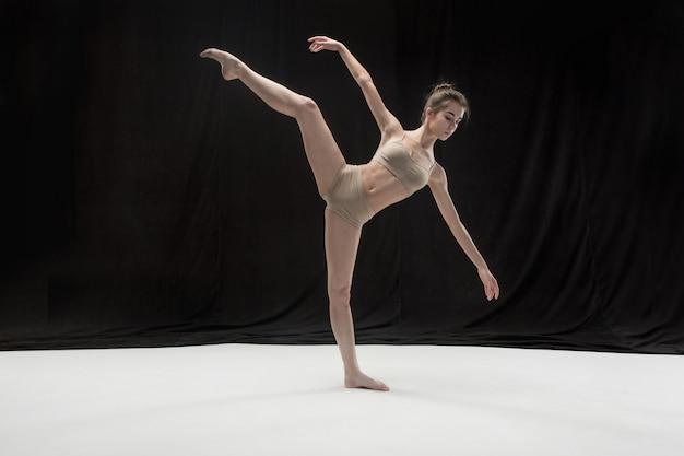 Joven bailarina adolescente en el espacio del piso blanco.