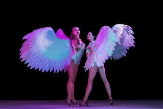 Joven bailarina con alas de ángel en luz de neón en pared negra