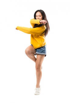 Joven bailarina asiática sobre pared blanca aislada