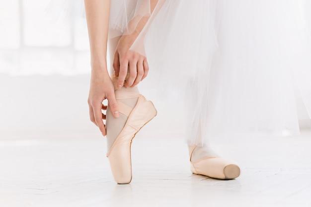 Joven bailarina bailando, primer plano en las piernas y los zapatos, de pie en posición de punta.
