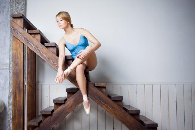 Joven bailarina de ballet atar cintas en su pointe.