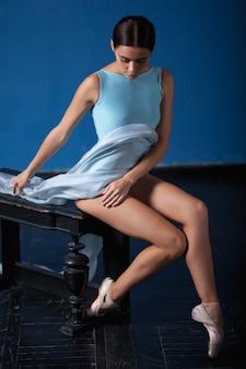 Joven bailarina de ballet moderno posando sobre fondo azul