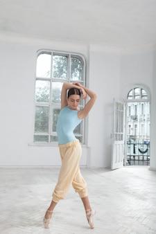 Joven bailarina de ballet moderno posando sobre fondo blanco.