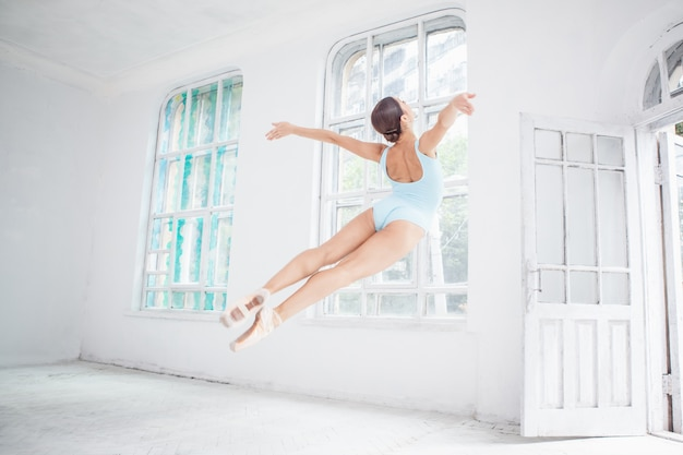 Joven bailarina de ballet moderno saltando sobre la pared blanca