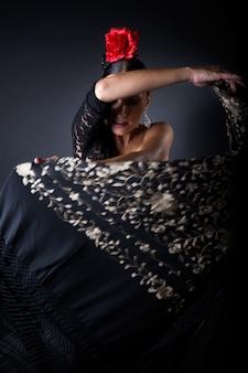 Joven bailarina de flamenco en hermoso vestido sobre fondo negro.