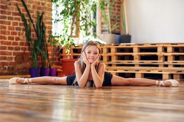 Una joven bailarina haciendo cordel en el salón de baile.