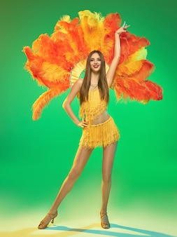 Joven bailarina hermosa posando en la pared verde