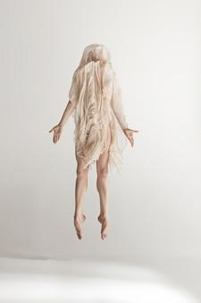 Joven bailarina hermosa en traje de baño beige bailando en gris