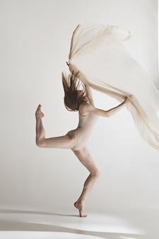 Joven bailarina hermosa en traje de baño beige bailando