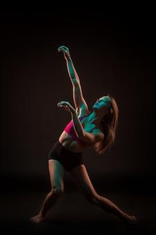 Joven bailarina hermosa en vestido beige bailando en negro