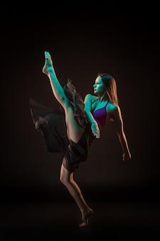 Joven bailarina hermosa en vestido beige bailando en la pared negra