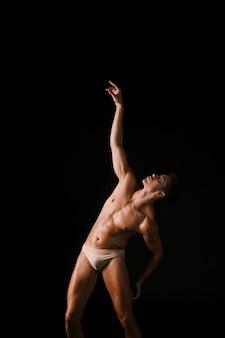 Joven bailarina mirando el brazo levantado