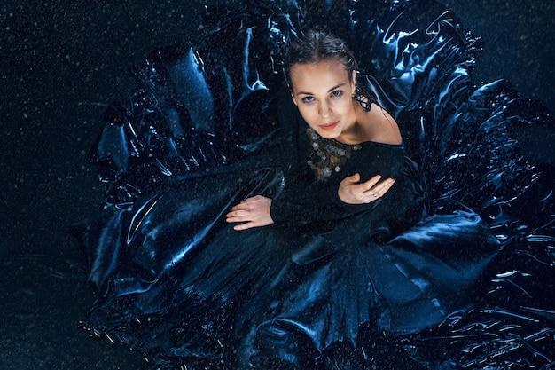 La joven bailarina moderna hermosa posando bajo gotas de agua