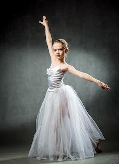 Joven bailarina mostrando los elementos de baile en un darkwall ballet. una pequeña bailarina