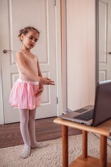 Joven bailarina practicando coreografía clásica durante la clase en línea en la escuela de ballet, autoaislamiento