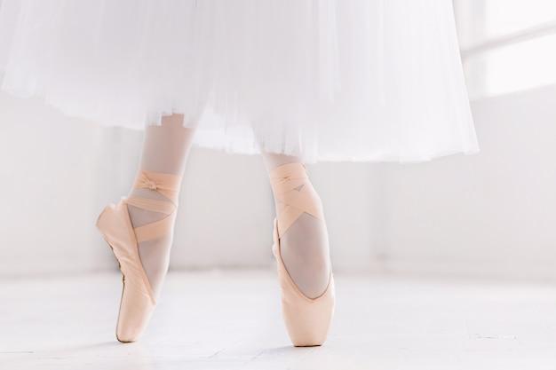 Joven bailarina, primer plano en las piernas y los zapatos, de pie en posición de punta.