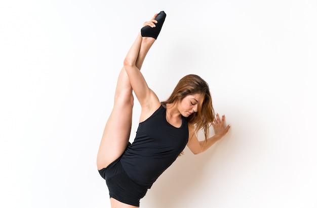 Joven bailarina sobre pared blanca aislada