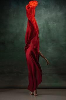 Joven bailarina tierna elegante en espacio de estudio verde oscuro con tela roja