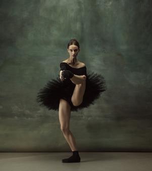 Joven bailarina tierna elegante en estudio oscuro