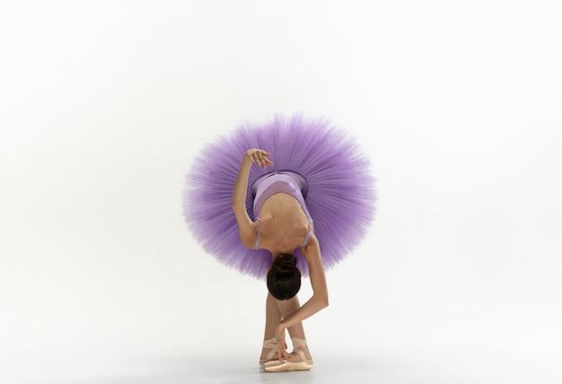 Joven bailarina tierna elegante en la pared blanca