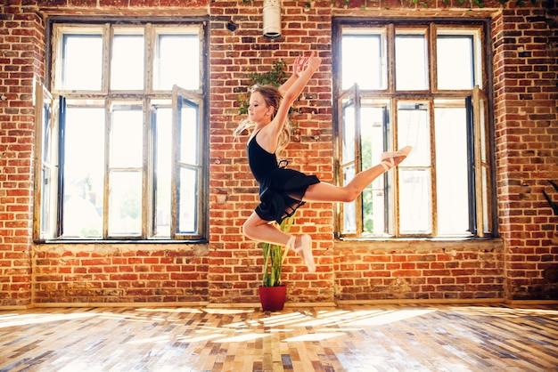 Joven bailarina en tutú negro practicando movimientos de baile.