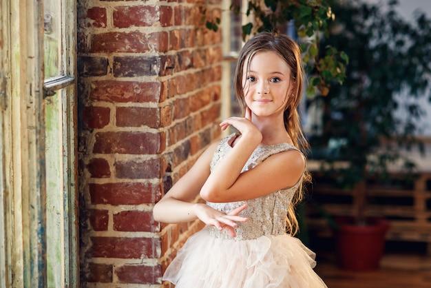 Joven bailarina en tutú y zapatillas de punta practicando movimientos de baile en la sala de baile.