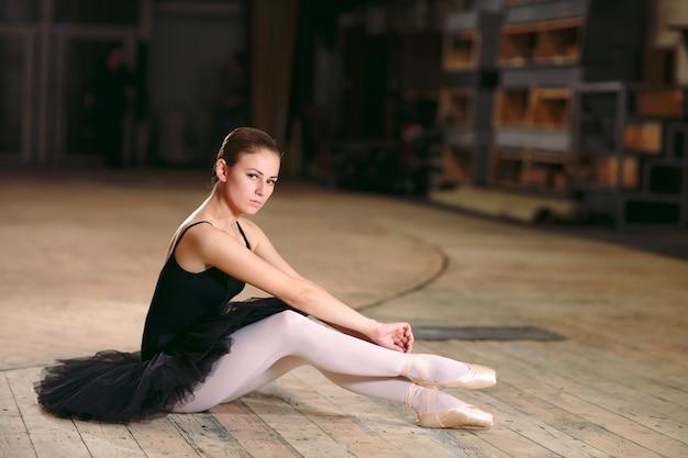 Joven bailarina vestida de negro entrena detrás de escena.