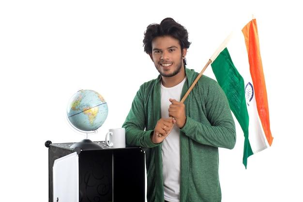 Joven con bandera india o tricolor con globo terráqueo sobre fondo blanco.