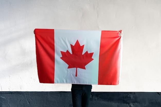 Un joven con una bandera nacional de canadá sobre el patriotismo y los sentimientos de orgullo de soulders