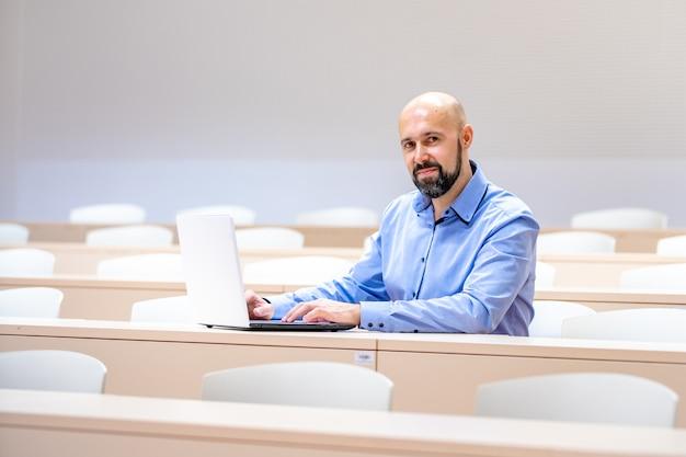 Joven con barba en el aula con portátil blanco