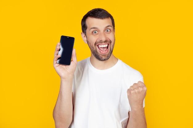 Joven con barba con una camiseta blanca muestra la pantalla de un teléfono inteligente, grita con orgullo y celebra la victoria y el éxito.