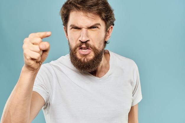 Un joven con barba en una camiseta muestra diferentes emociones, diversión, tristeza, ira en el estudio en el fondo