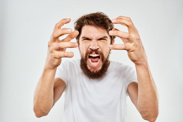 Un joven con barba en una camiseta muestra diferentes emociones, diversión, tristeza, ira.