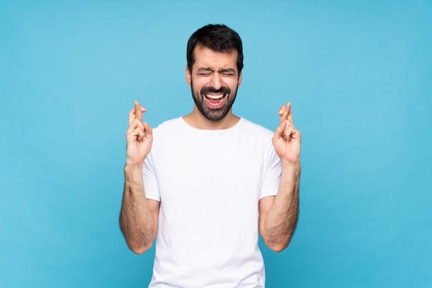 Joven con barba sobre azul aislado con cruzar los dedos