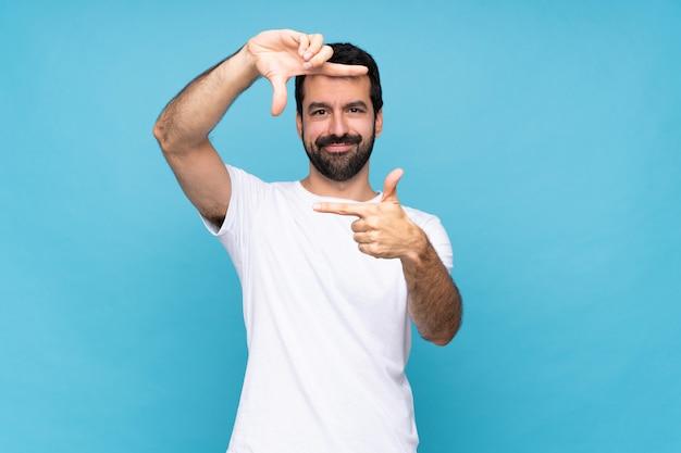 Joven con barba sobre cara de enfoque azul aislado, símbolo de encuadre