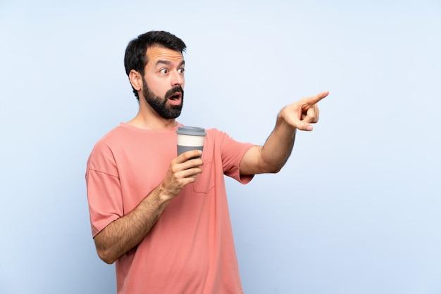 Joven con barba sosteniendo un café para llevar en azul apuntando lejos