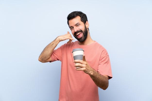Joven con barba sosteniendo un café para llevar haciendo gesto de teléfono y apuntando al frente