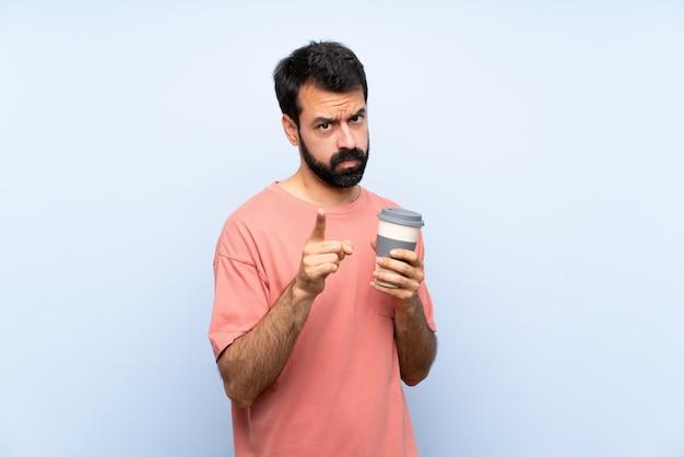 Joven con barba sosteniendo un café para llevar sobre azul aislado frustrado y apuntando hacia el frente