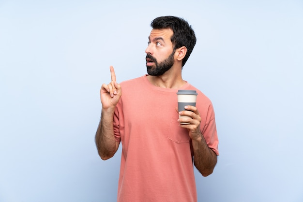 Joven con barba sosteniendo un café para llevar sobre azul aislado pensando en una idea apuntando con el dedo hacia arriba